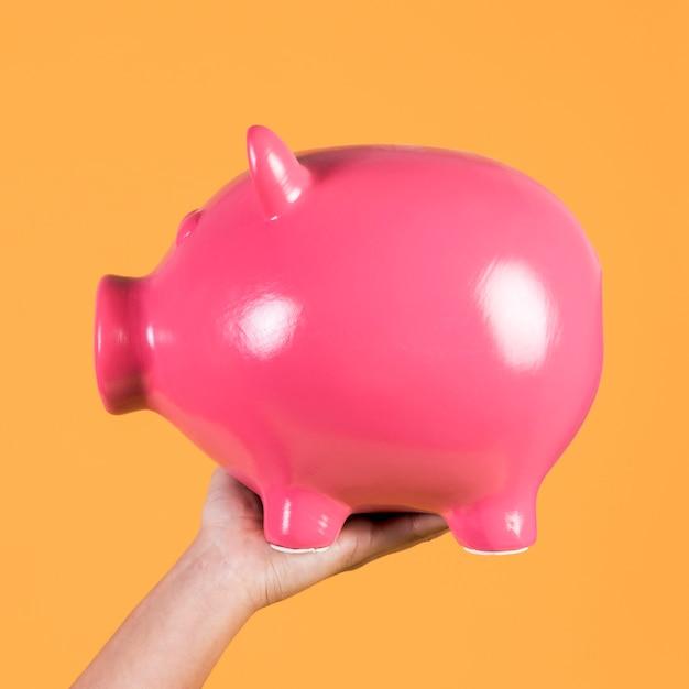 Mão da pessoa, mostrando o conceito de poupança com piggybank Foto gratuita