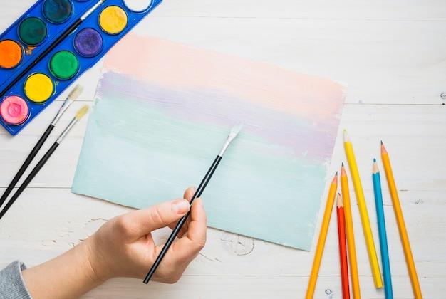 Mão da pessoa, pintura em papel com pincel e aquarela sobre a mesa Foto gratuita