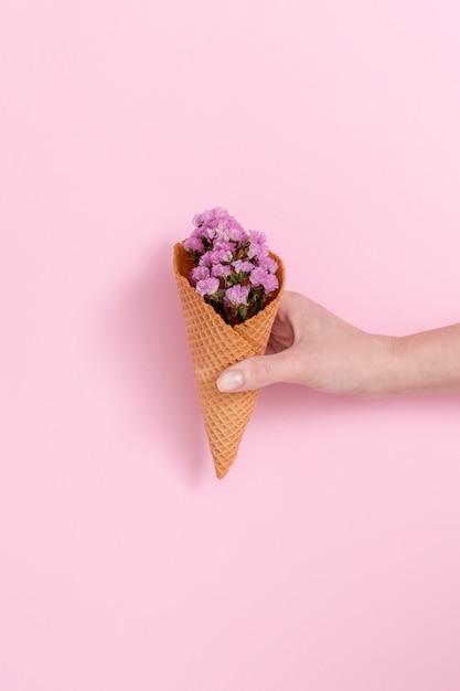 Mão da pessoa segurando buquê de flores roxas no cone waffle na frente de fundo rosa Foto gratuita