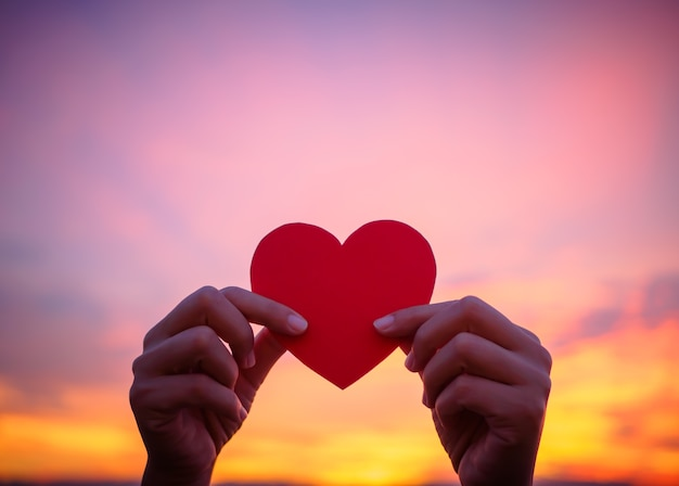 Mão da silhueta que guarda o coração bonito durante o fundo do por do sol. Foto Premium