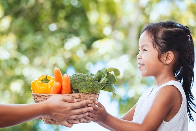 Mão de agricultor mãe dando cesta de legumes para mão de menina pequena criança no jardim Foto Premium