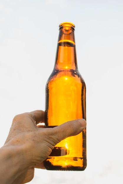 Mão de ângulo baixo com a garrafa de cerveja aberta Foto gratuita