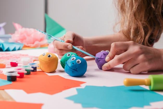 Mão de artista feminina fazendo caretas cartoon usando equipamento artesanal Foto gratuita