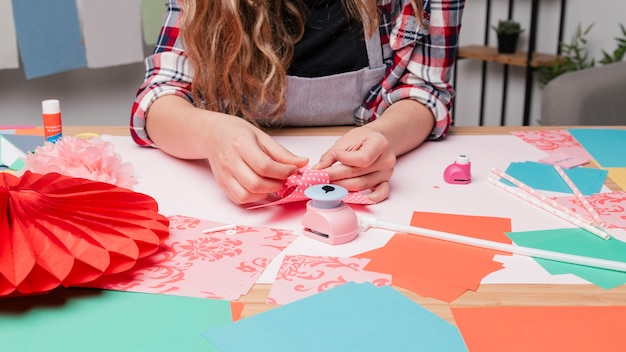 Mão de artista feminina fazendo cata-vento usando papel origami Foto gratuita