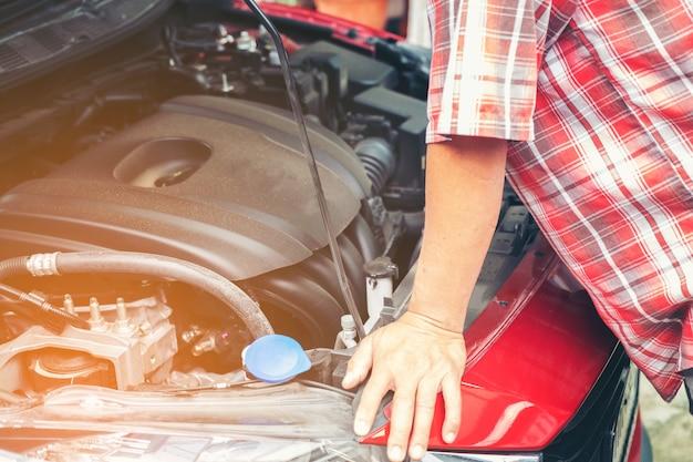 Mão de auto mecânica com uma chave inglesa. mecânico do reparo do carro que verifica o motor de automóveis no serviço dos carros. Foto Premium