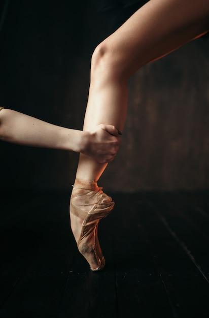 Mão de bailarina segura o pé em sapatilhas de ponta, piso de madeira preta. bailarina vestida de vermelho e preto praticando dança no palco do teatro Foto Premium