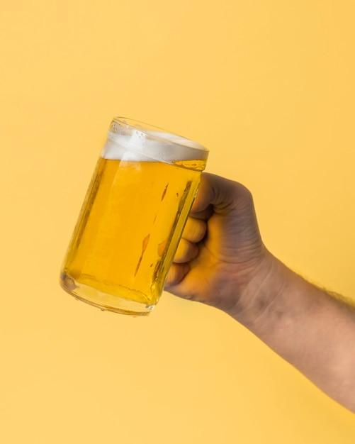 Mão de baixo ângulo, segurando uma cerveja com cerveja Foto Premium