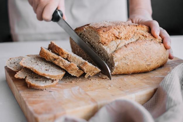Mão de baker fatiar pão fresco com faca Foto gratuita