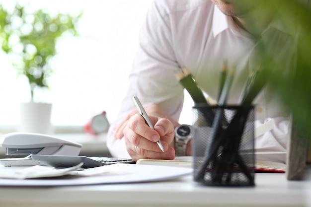 Mão de balconista masculino segurando caneta prata escrevendo algo Foto Premium