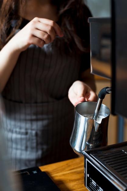 Mão de barista feminino cozinhar leite para latte em jarra de aço inoxidável Foto gratuita