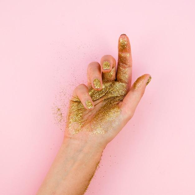 Mão de close-up com glitter dourado Foto gratuita
