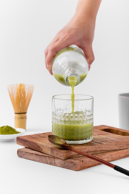 Mão de close-up, derramando chá matcha em vidro Foto gratuita