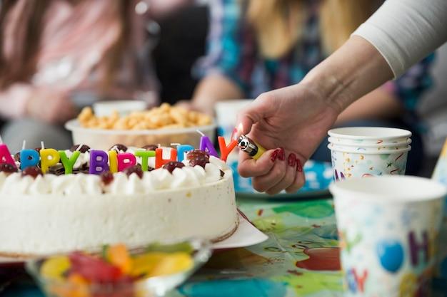 Mão de colheita acendendo velas no bolo de aniversário Foto gratuita