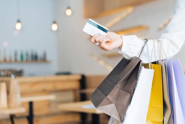 Mão de colheita com sacos de papel e cartão de crédito Foto Premium