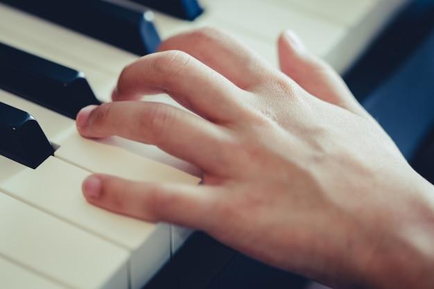 Mão de criança, pressionando a tecla piano para o conceito de música Foto Premium