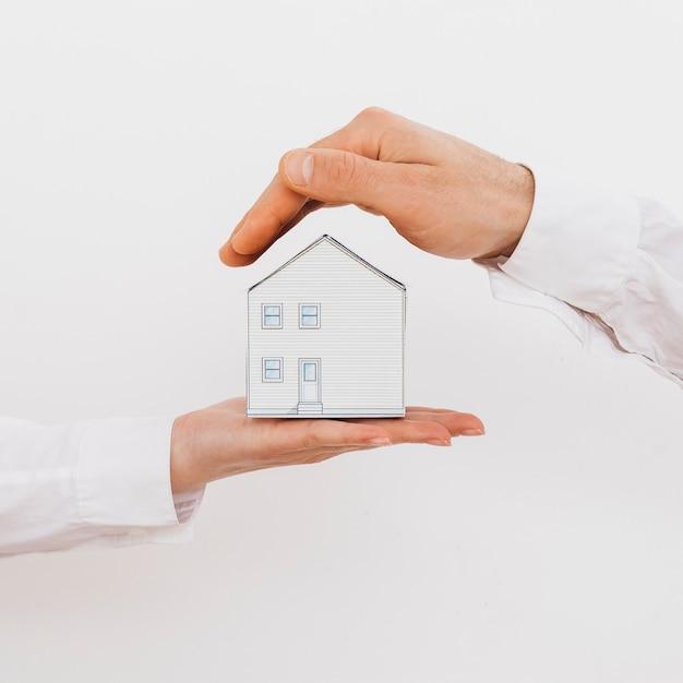 Mão de dois empresários, protegendo a casa de modelo em miniatura, isolada no fundo branco Foto gratuita