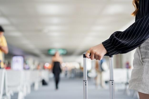 Mão de empresária tocando bolsa bagagem Foto Premium