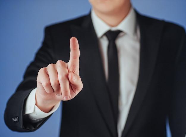 Mão de empresário, apontando no espaço vazio em fundo preto Foto Premium