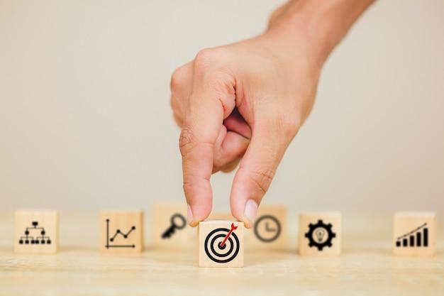 Mão de empresário colocando o bloco de cubo de madeira no topo com o alvo de ícone Foto Premium
