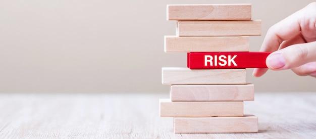 Mão de empresário, colocando ou puxando o bloco de madeira com palavra de risco na torre. conceitos de planejamento, gerenciamento, solução, oportunidade e estratégia de negócios Foto Premium