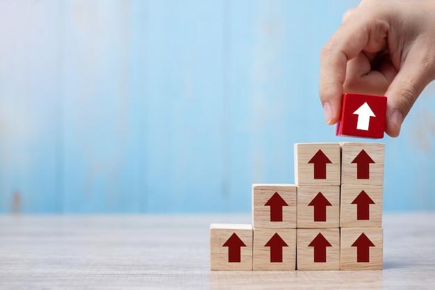 Mão de empresário, colocando ou puxando o bloco vermelho com seta e crescimento seta para cima na mesa Foto Premium