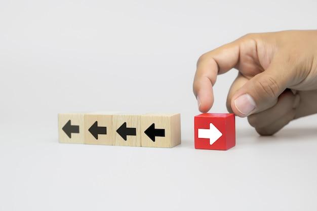 Mão de empresário escolhe blog de brinquedo de madeira com ícones de ponta de seta apontando para direções opostas Foto Premium
