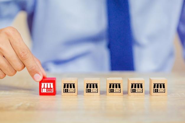 Mão de empresário escolher blog de madeira com marketing de franquia. Foto Premium