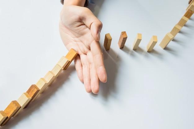 Mão de empresário pára dominó continuamente derrubado ou risco com copyspace Foto gratuita