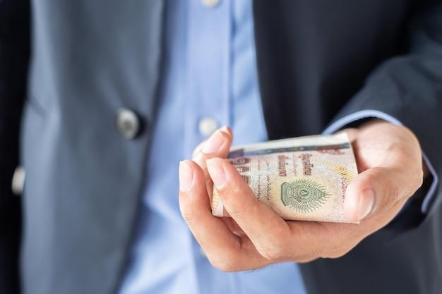 Mão de empresário segurando a pilha de notas de baht tailandês. Foto Premium