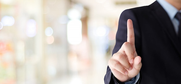 Mão de empresário tocando sobre fundo de escritório borrão, fundo de negócios, banner Foto Premium