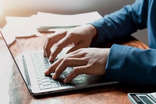 Mão de empresário usando laptop trabalhando no escritório Foto Premium