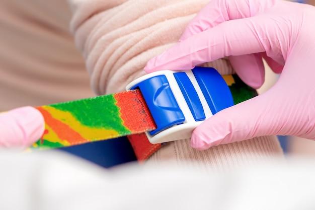 Mão de enfermeira apertando torniquete no braço Foto Premium