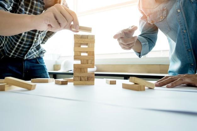 Mão de engenheiro jogando um jogo de torre de madeira de blocos (jenga) no projeto de arquitetura ou arquitetônico Foto gratuita