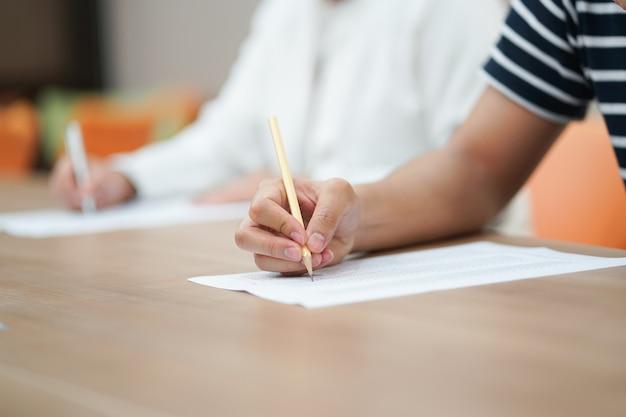 Mão de estudante, usando o lápis para fazer exame de texto Foto Premium