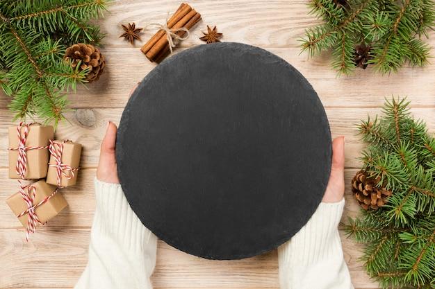 Mão de famale segurar pedra ardósia preta redonda sobre madeira Foto Premium