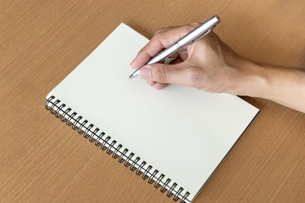 Mão de homem com caneta prepare-se para escrever no caderno Foto Premium
