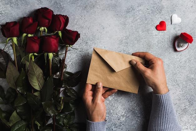 Mão de homem de dia dos namorados segurando a carta de amor de envelope com cartão Foto gratuita
