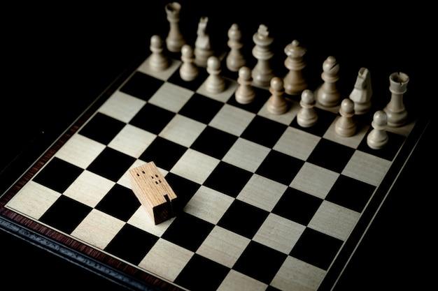 Mão de homem de negócios, movendo-se de xadrez para o edifício e casa modelos no jogo de xadrez Foto Premium