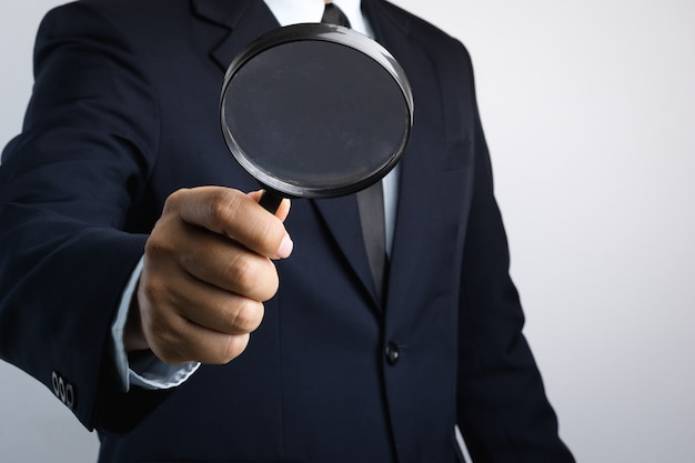 Mão de homem de negócios segurando a lupa para inspeção Foto Premium