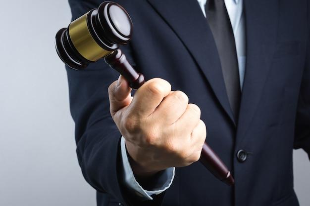 Mão de homem de negócios segurando o martelo do juiz de madeira como um sinal de lei ou justiça Foto Premium