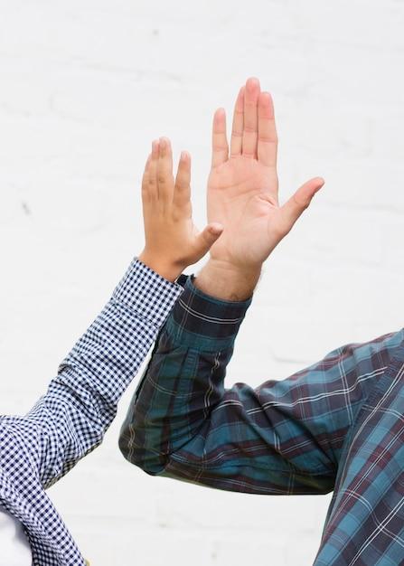 Mão de homem e mão de menino bater cinco Foto gratuita