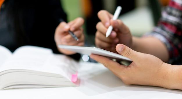 Mão de homem estudante segurando o tablet e usando a caneta para perguntar Foto Premium