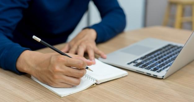 Mão de homem estudante usando lápis para escrever no caderno Foto Premium