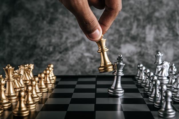 Mão de homem jogando xadrez para planejamento de negócios e comparação de metáfora, foco seletivo Foto gratuita