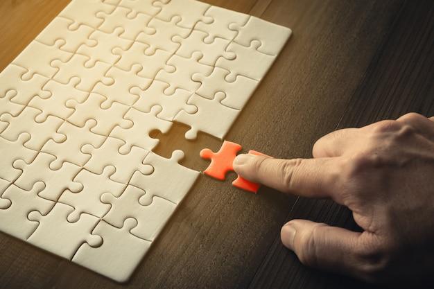 Mão, de, homem negócios, segurando, último, pedaço, quebra-cabeças, negócio, sucesso, conceito Foto Premium