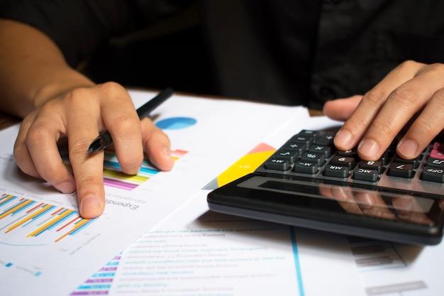 Mão de homem segurando a caneta e cálculo de números. Foto Premium
