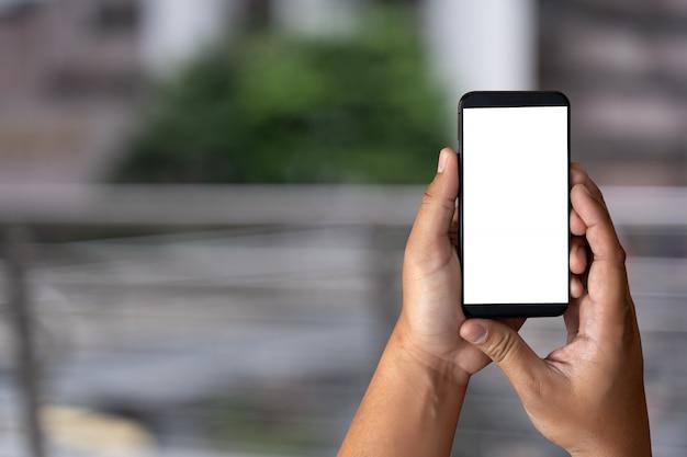 Mão de homem segurando a maquete de tela do smartphone preto Foto Premium