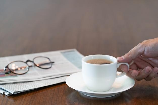 Mão de homem segurando a xícara de café quente pela manhã Foto Premium