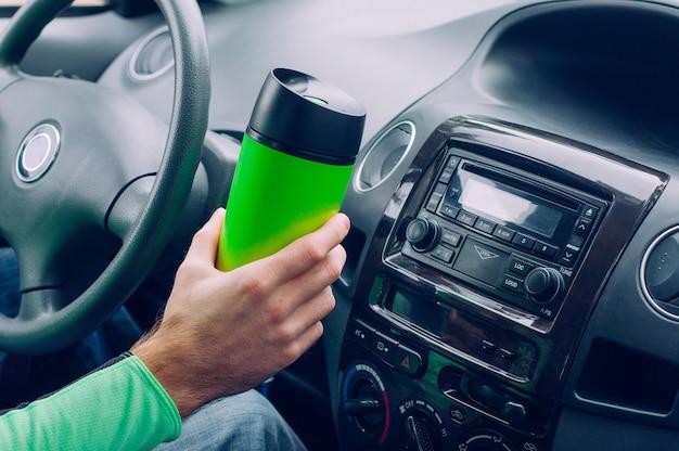 Mão de homem segurando caneca térmica Foto Premium