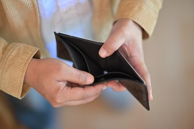 Mão de homem segurando carteira vazia Foto Premium